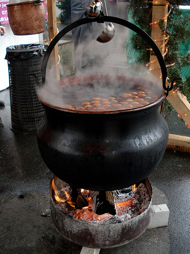 photo of a large cauldron of mulled wine over a fire.